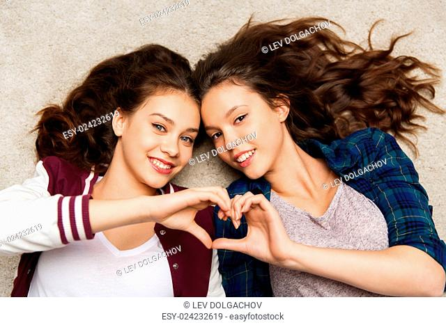 people, friends, teens and friendship concept - happy smiling pretty teenage girls lying on floor showing heart sing