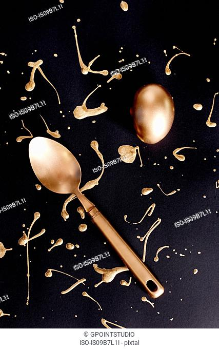 Overhead view of gold painted easter egg and spoon with splatters on black background
