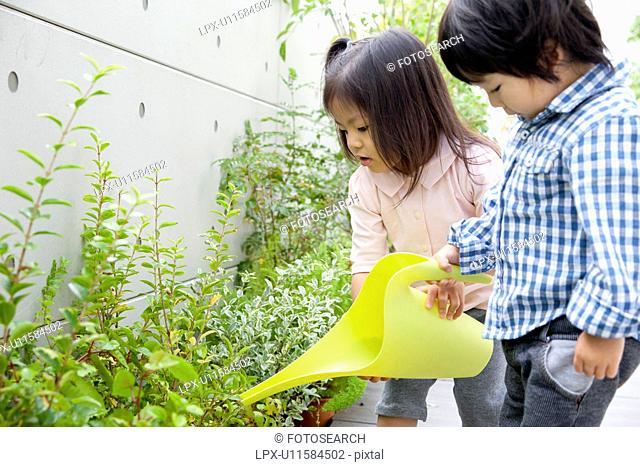 Two children watering plants