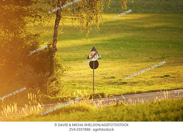 Landscape of a traffic sign beside a road on a evening in late summer