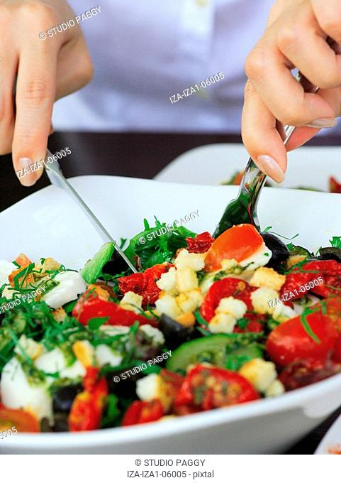 Mid section view of a woman eating salad