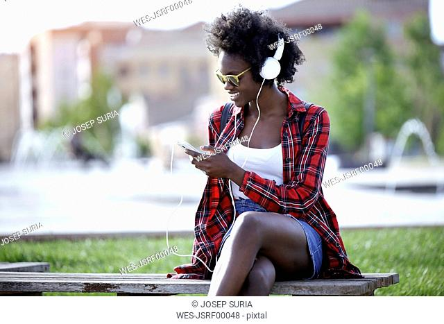 Smiling young woman sitting on bench in city park listening music with headphones