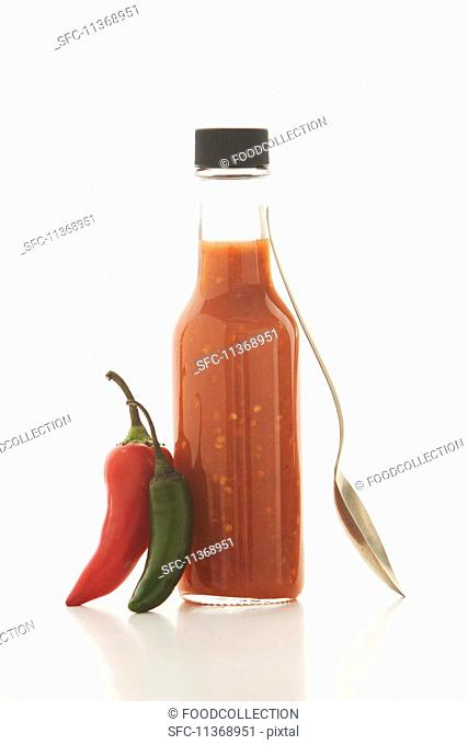 A bottle of chili sauce, fresh chilli peppers and a spoon