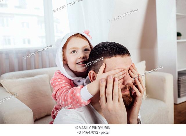 Daughter covering father's eyes while playing in living room at home