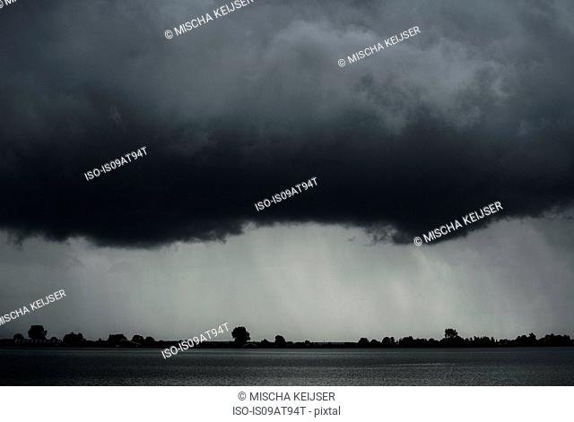 Black and white image of heavy rainfall over lake during thunderstorm