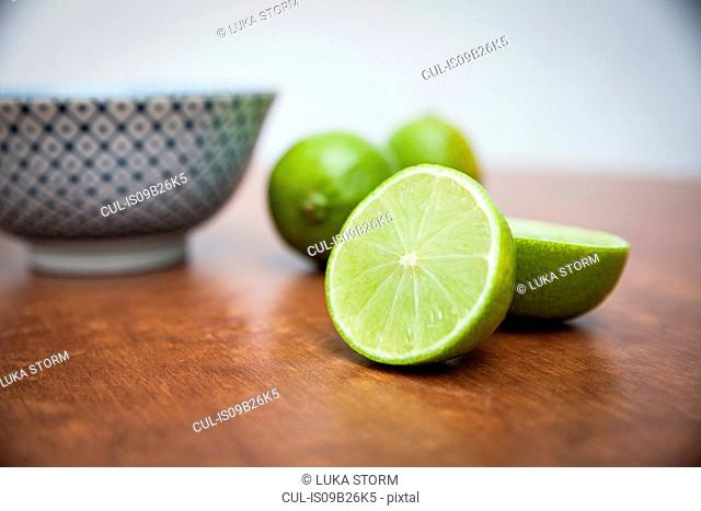 Halved and whole limes on wooden table