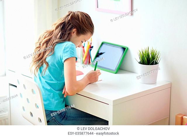people, children and education concept - happy girl with tablet pc computer writing to notebook at home