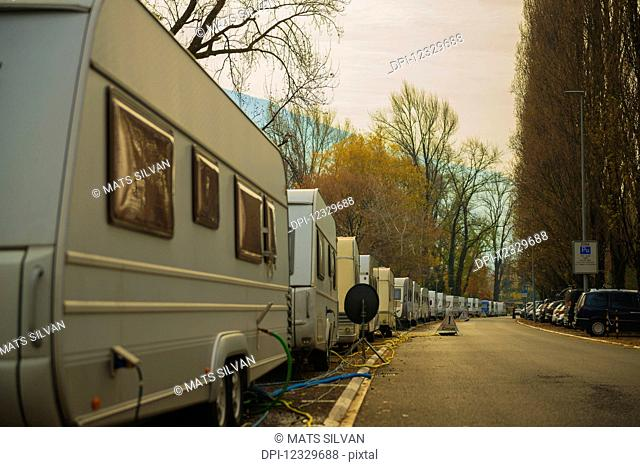 Camping Trailers Parked In A Row Along A Street With Electrical Lines And Hoses For Hook Up; Locarno, Ticino, Switzerland