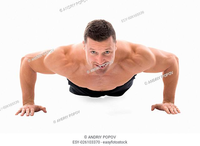 Determined muscular man doing push ups against white background