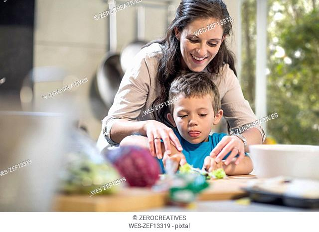 Mother and son chopping vegetables in kitchen