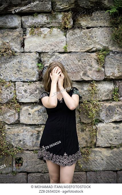 Young woman hiding face with hands outdoors