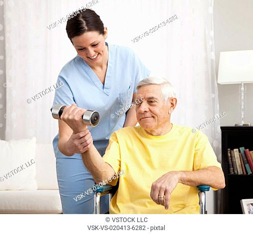 Female nurse assisting senior man exercising in retirement home