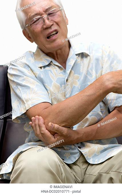 A senior man covering his hand on his elbow