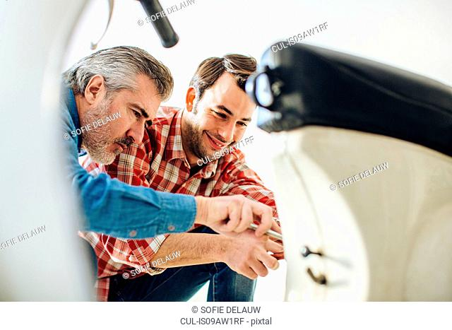Mature man and adult son to repairing moped in garage