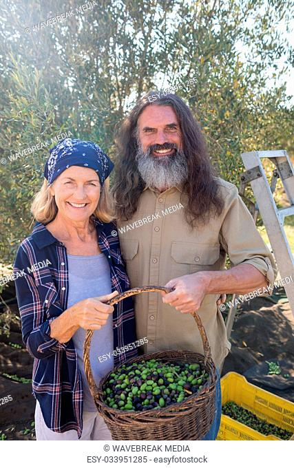 Portrait of happy couple holding basket full of olives