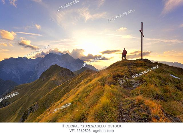 A hiker admires the sunset on Marmolada group from the grassy summit of Migogn Mount, Dolomites, Marmolada group, Rocca Pietore, Belluno province, Veneto, Italy