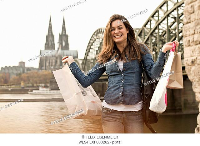 Germany, Cologne, happy young woman with shopping bags in front of Hohenzollern Bridge