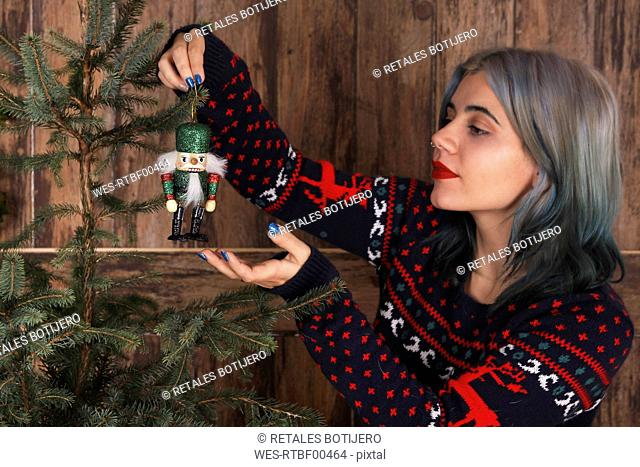 Young woman decorating Christmas tree with nutcracker figure