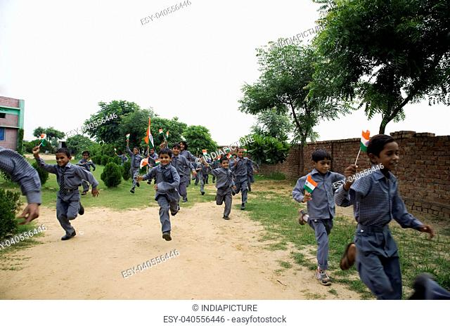 School boys running with the Indian flag
