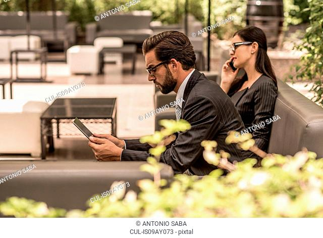 Businessman using digital tablet on hotel garden sofa, Dubai, United Arab Emirates