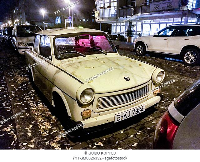 Berlin, Germany. A vintage and historical Trabant car parked alongside a sidewalk in a neighbourhood street at night, after the owner returned home from work