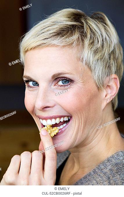 Smiling woman eating snack