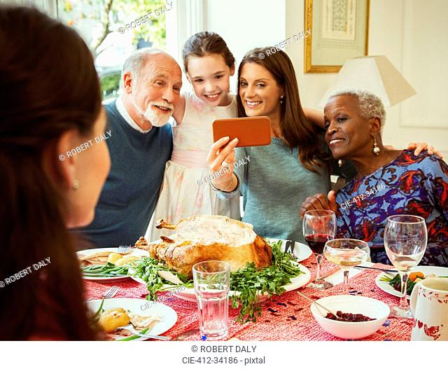 Multi-ethnic multi-generation family with camera phone taking selfie at Christmas dinner table