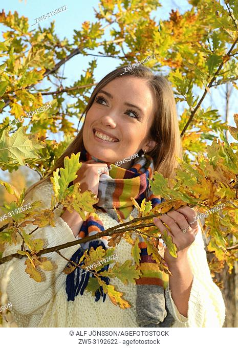 Portrait on a young smiling woman in a autumn colored forest in Ystad, Scania, Sweden