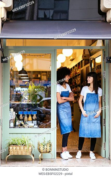 Two smiling women standing in entrance door of a store