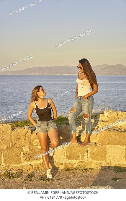 two friends sitting on ancient ruins at seaside, hanging out. In Chersonissos, Crete, Greece