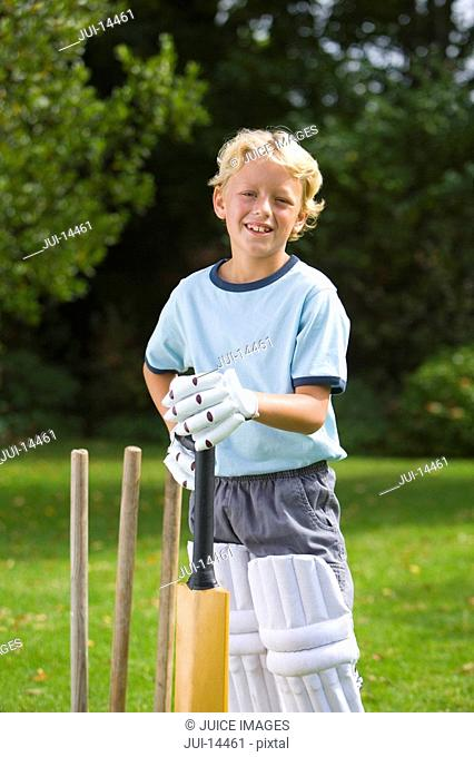 Boy 6-8 playing cricket, smiling, portrait