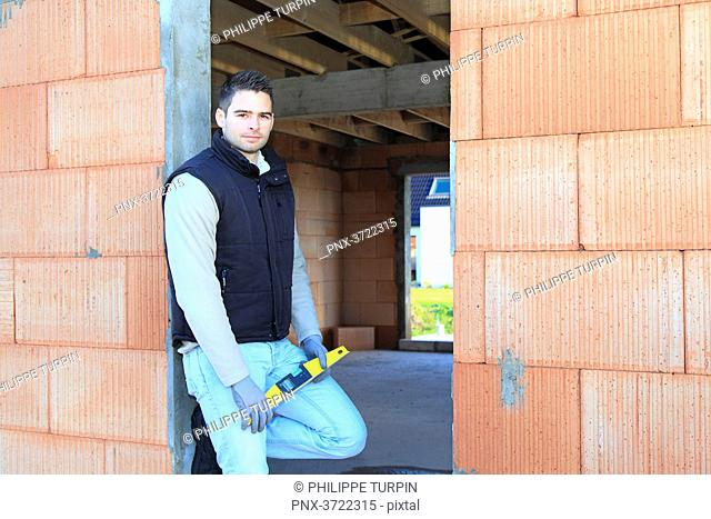 France, young working person in a house in construction