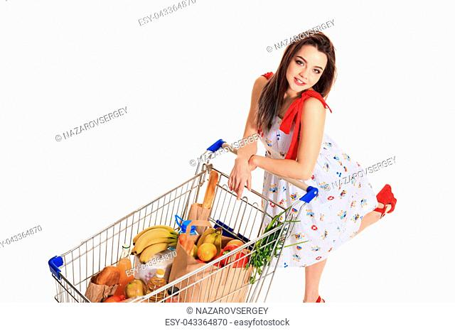 High angle view of girl smiling at camera while pushing a shopping cart full with groceries isolated on white background