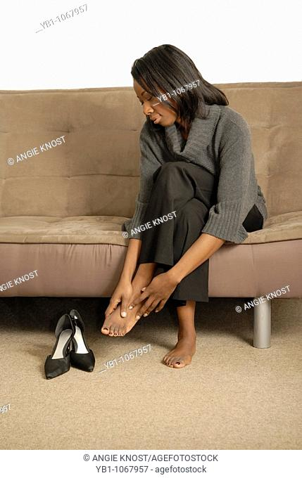 Attractive woman taking off her shoes and massaging sore feet