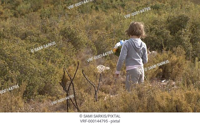 Girl 7-8 running through meadow with flowers in hands