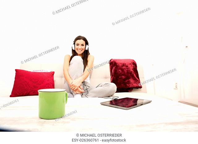 Young beautiful woman listening to music with headphones and a Tablet PC at home.