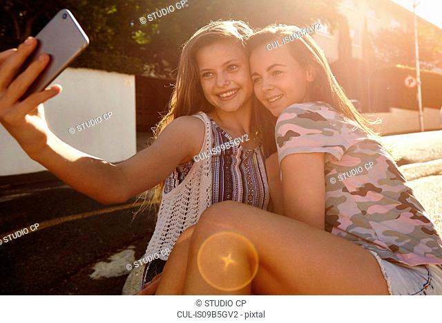 Teenage girls taking selfies in street, Cape Town, South Africa