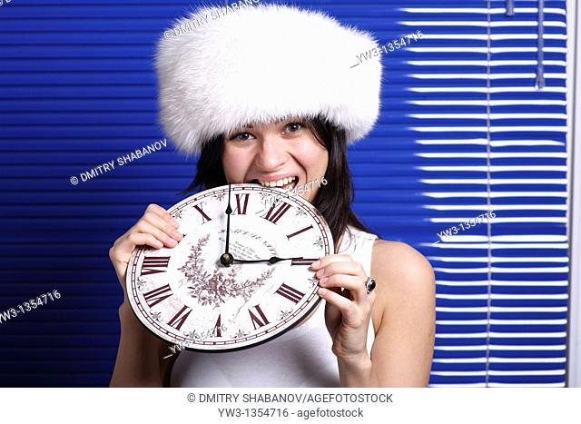 Smiling beautiful womanbiting the clock against louvers