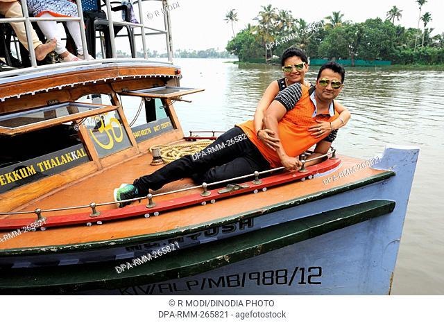 couple lying on deck of boat backwater, Munnar, Kerala, India, Asia, MR#801B, MR#802B