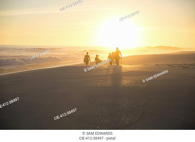 Silhouette family walking on sunny summer sunset beach