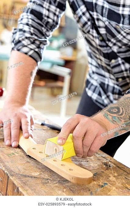 Craftsman using sanding paper on a guitar neck in a workshop for wood. Hard working man with tattoo working with musical instruments