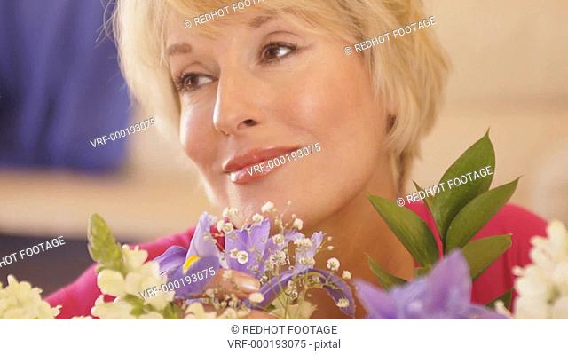 Close up dolly shot of woman smelling flower scent