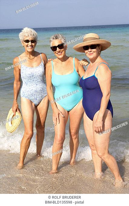 Senior women standing in waves on beach