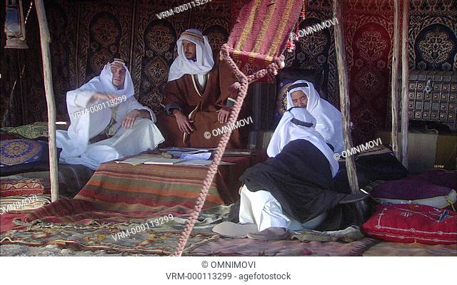 WS Lawrence of Arabia and three young-middle aged males dressed in Arabic traditional clothing sitting on carpets in tent with Islamic patterned curtains behind...