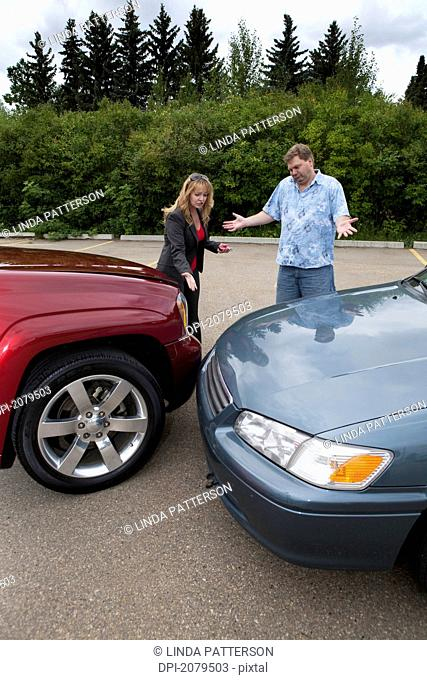A man and woman looking at the bumpers of their vehicles after a collision, edmonton alberta canada
