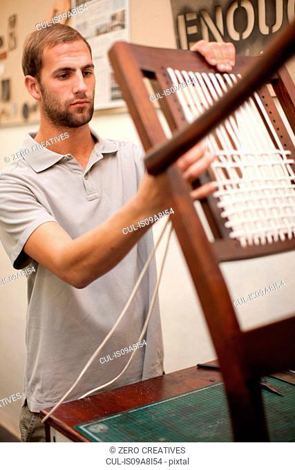 Man weaving chair back