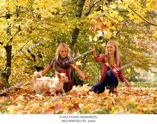 Austria, Sisters playing with dog in autumn