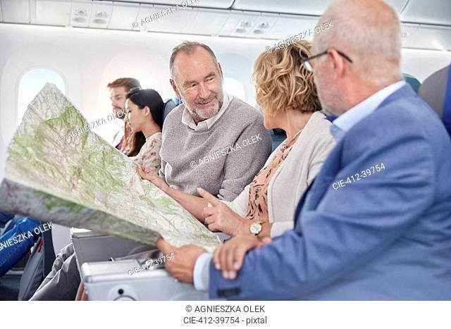 Mature friends looking at map on airplane