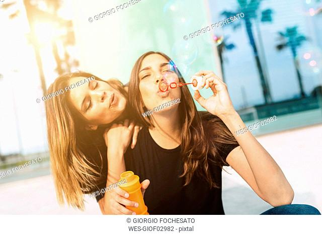 Two happy young women blowing soap bubbles