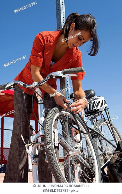 Hispanic woman locking bicycle